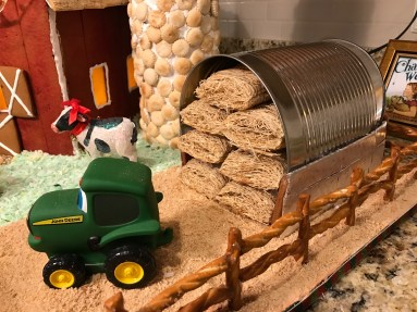 For the hoop house, I cut a #10 tin can and stuffed it with original shredded wheat cereal. For the grain silo, I stacked two oatmeal containers and covered them with frosting and oyster crackers, and put sticks of gum on the top to create the roofing. I found the perfect little animal ornaments at Hobby Lobby and the John Deere tractor toy at IFA.