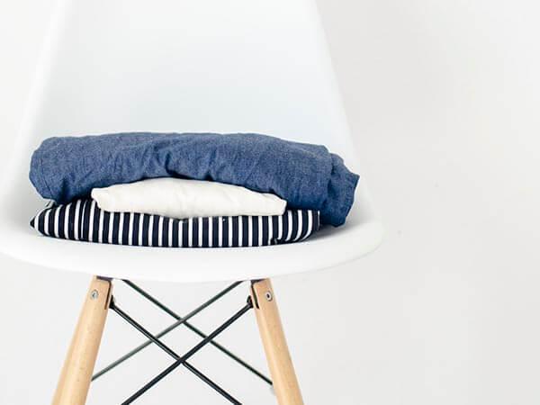 Kleidungsstücke auf Eames Chair. Capsule Wardrobe