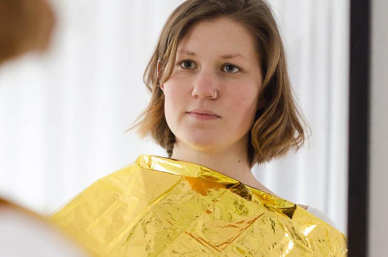 Farbtypen Bestimmung vor Spiegel mit Gold- und Silberfolie. Die Rettungsdecke zeigt die goldene Seite.