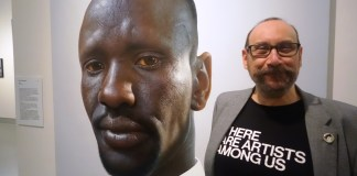 Artist Nick Stathopoulos with his portrait of Deng Adut
