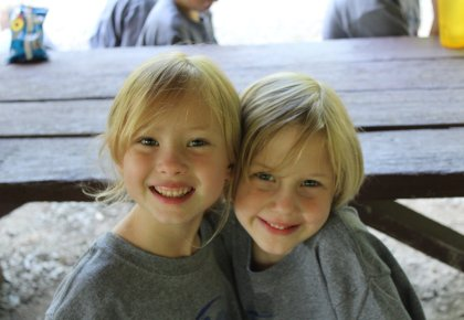 Two children hugging at a picnic table