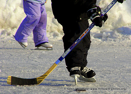 Photography of outdoor ice hockey stick and a pair of players.