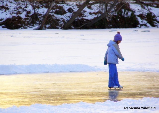 Photograph of a young child ice skating on a winter pond.