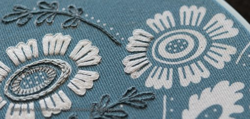 Using buttonhole stitch to create a simple yet effective flower on a clutch designed by Annes Orchard