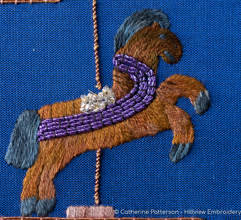 A stitched horse on a merry-go-round as part of the interpretation of the theme 'sensations'. Designed and stitched by Catherine of Hillview Embroidery. Find out more at hillviewembroidery.com