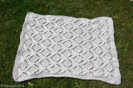 Chunky knit umaro blanket spread on grass