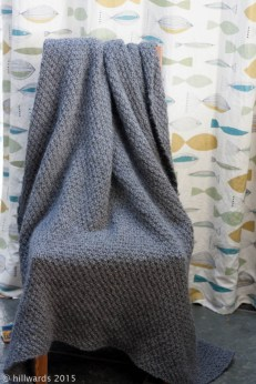 double seed stitch hand knit blanket draped over chair