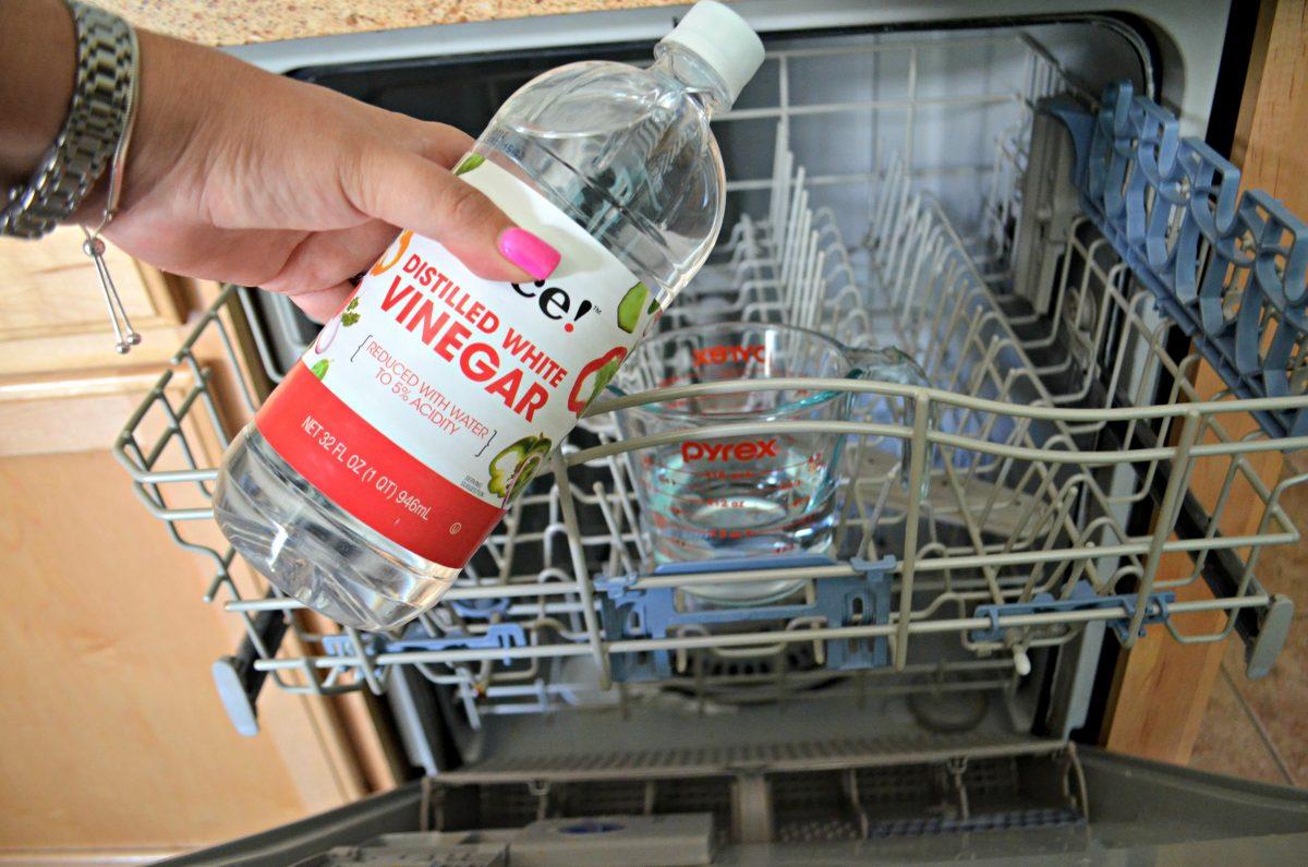 hand holding a bottle of vinegar over open dishwasher