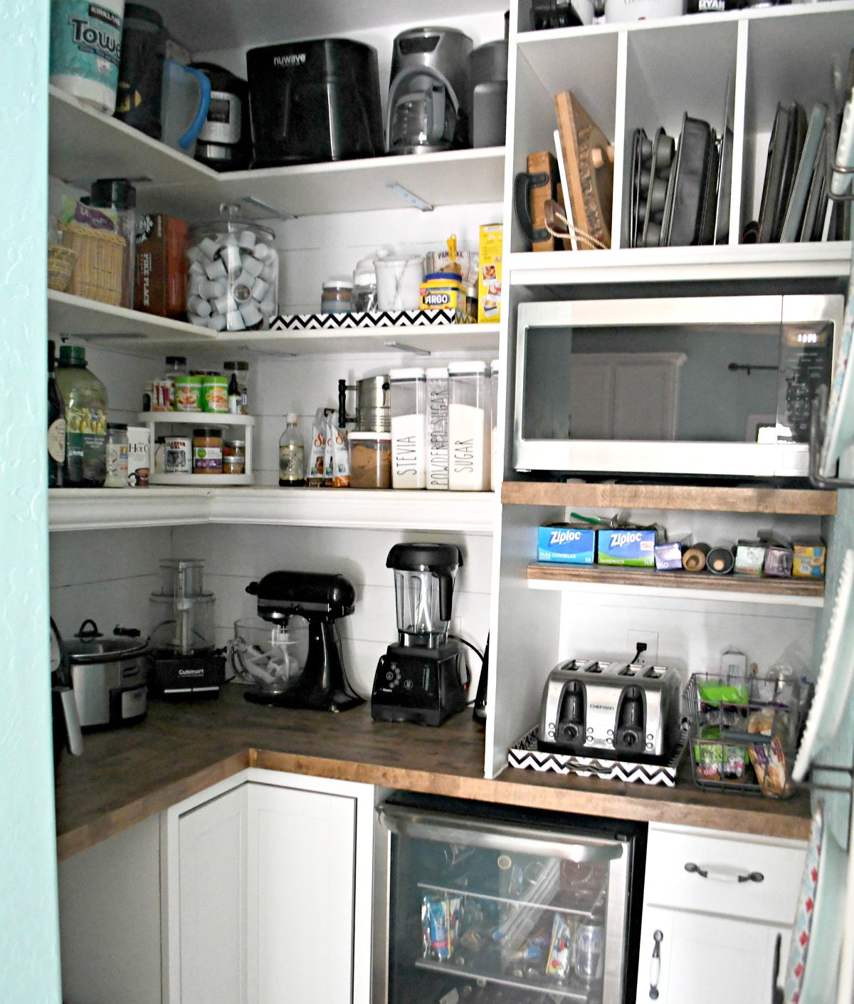 inside view of the pantry remodel with built in appliances, pantry goods, and pans