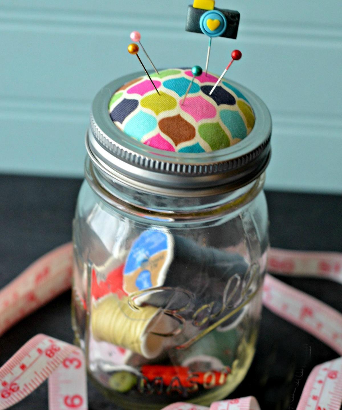 Mason jar with a pin cushion and sewing supplies