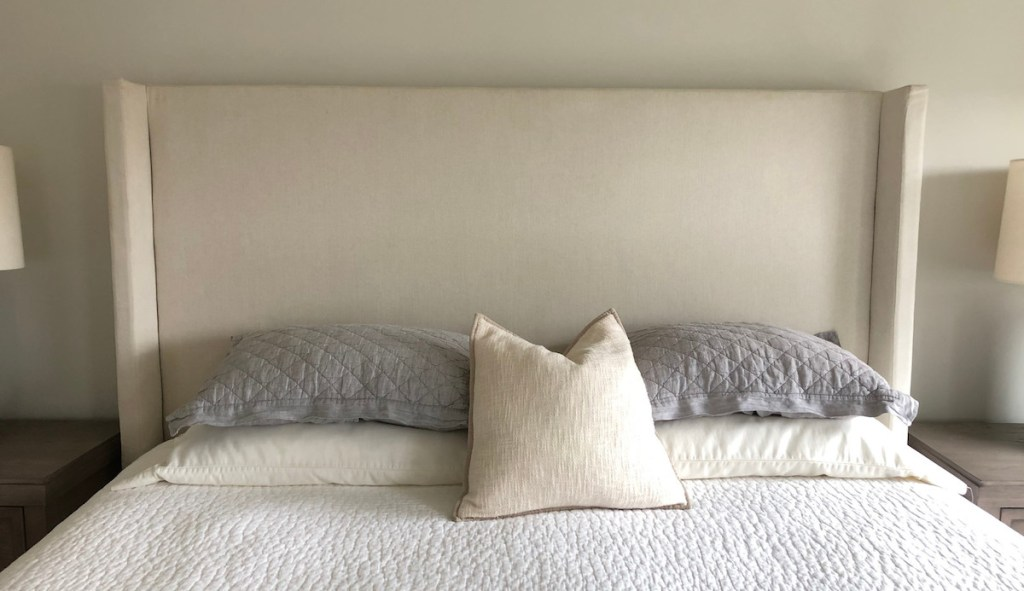 bed with five pillows gray and cream colored