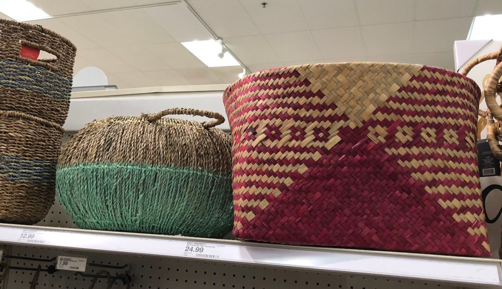 two seagrass woven baskets sitting on a shelf natural colored with blue green and burgundy