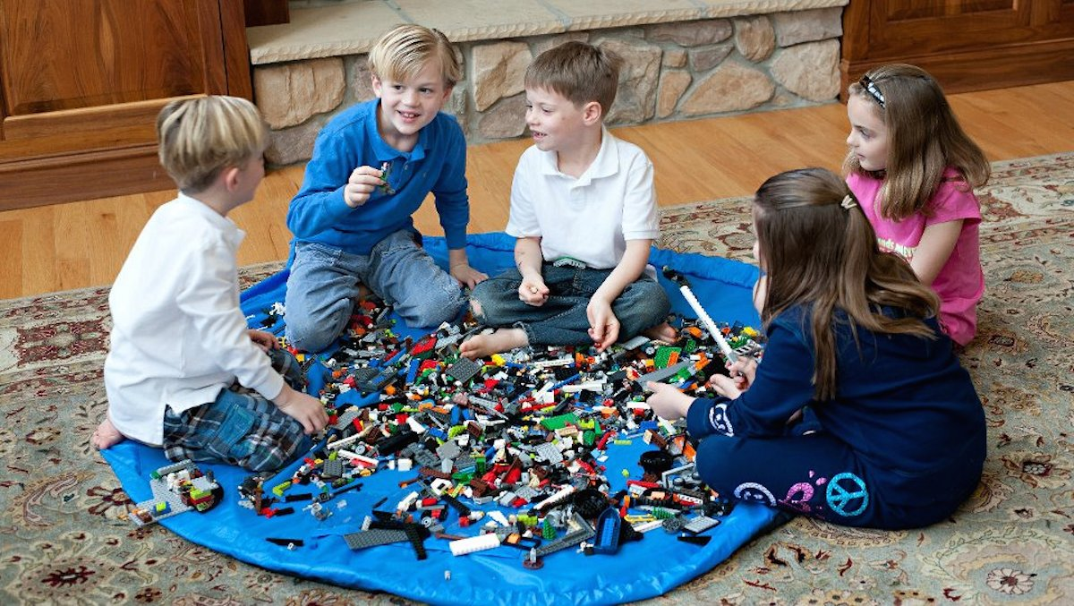 four kids playing on a blue at with legos