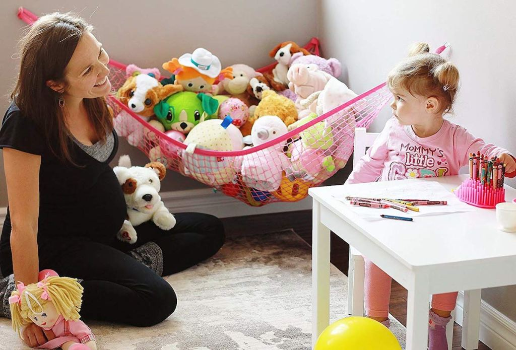 mom smiling at daughter with pink hammock in corner of room filled with stuffed animals