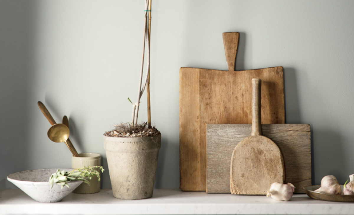 different sized cutting boards against a gray wall with planters