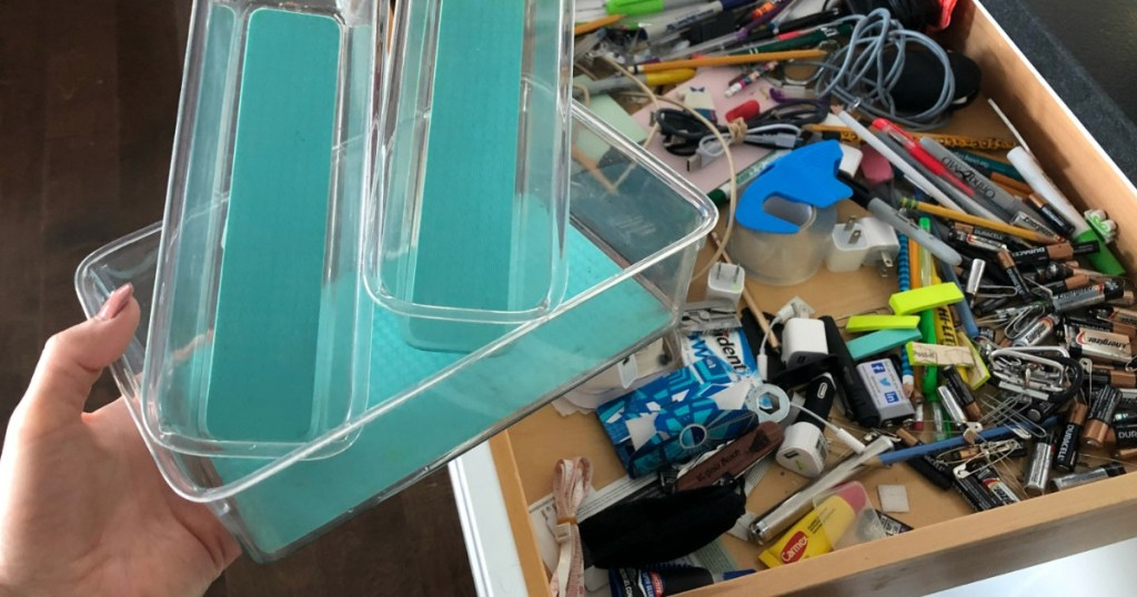 hand holding plastic organizers with messy junk drawer in the background
