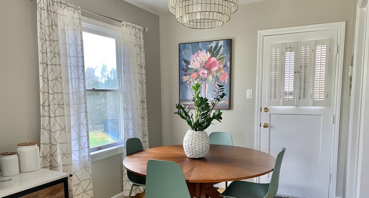 breakfast nook with floral artwork white curtains wood round table and blue green chairs