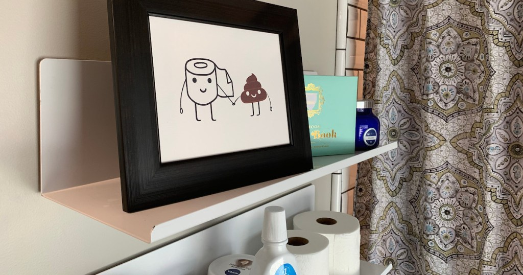 metal wall shelf in bathroom with toilet paper and poop emoji picture