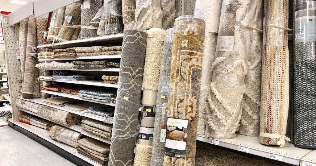 rolled rugs in store aisle leaning against shelves