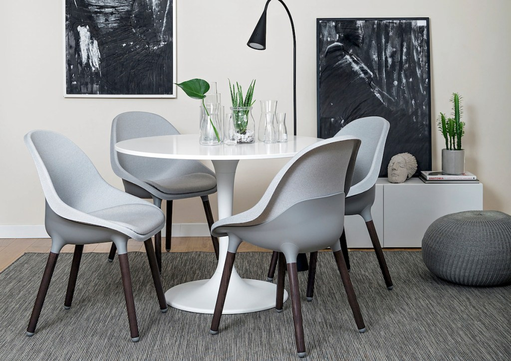 four gray modern chairs sitting at round white table
