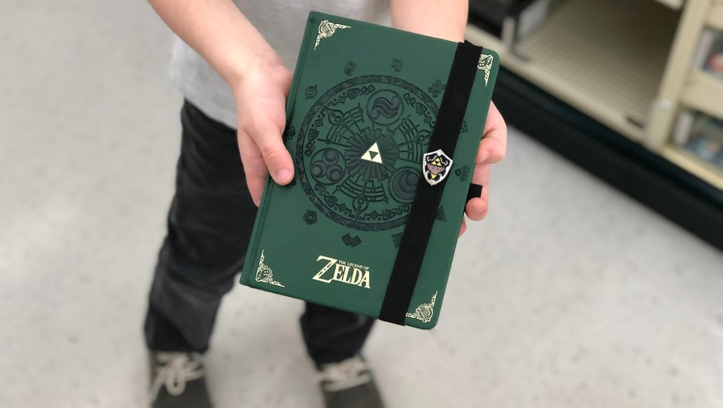 hands holding a dark green and gold zelda writing journal with shoes in background