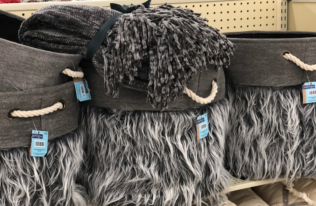 gray white faux fur baskets with gray blanket on top