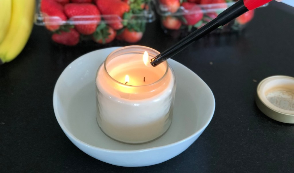 cream candle in white dish with water and fruit in the background
