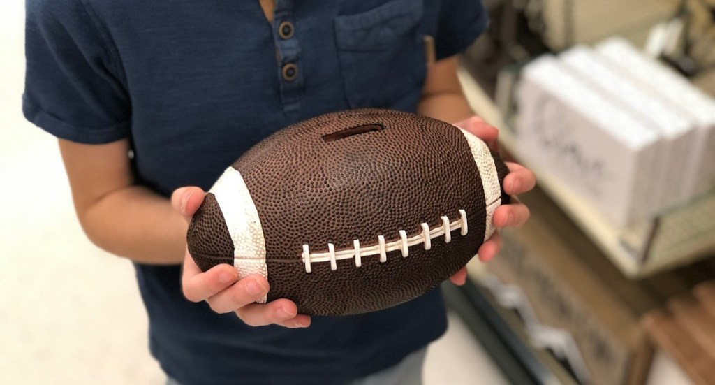 hands holding ceramic football bank