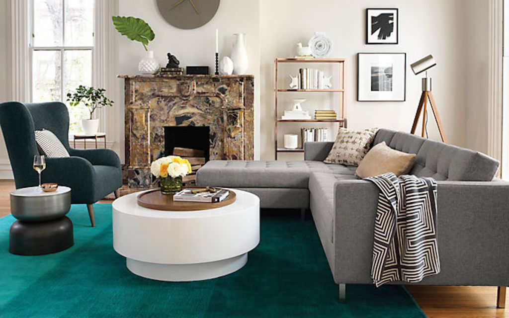 modern living room with white coffee table gray couch and teal colored rug