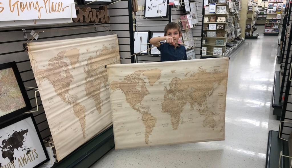 boys holding map tapestry in store aisle with maps hanging on shelf
