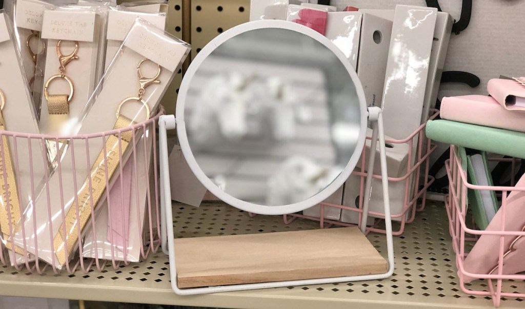 white round metal mirror on store shelf with pink decor
