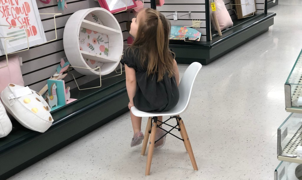 girl sitting on small modern white chair in store aisle