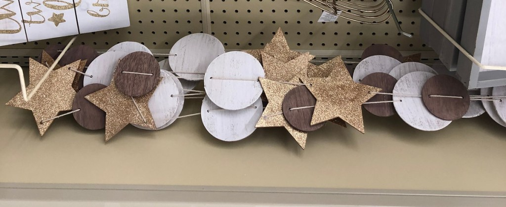 brown gold and white star and circle shaped banner garland laying on store shelf
