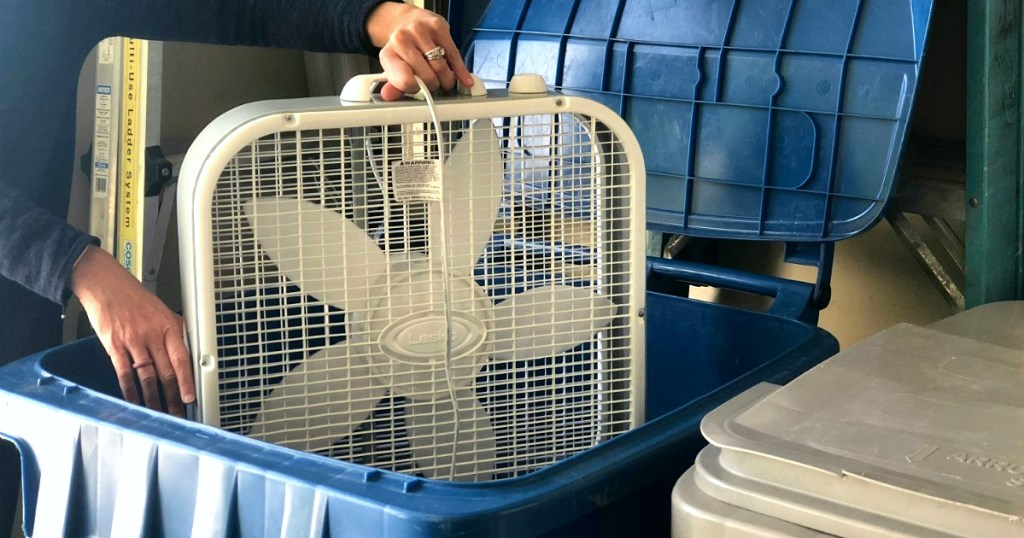 person holding white box fan over huge blue trashcan