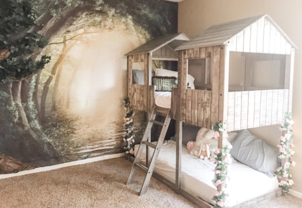 wood bunk bed with roof and forest mural on wall
