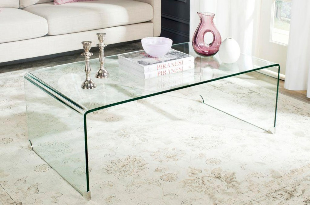 clear coffee table with silver candle sticks and pink vases and books