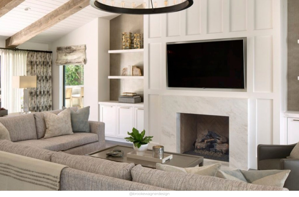 white board and battan fireplace with tv over top with large gray sectional