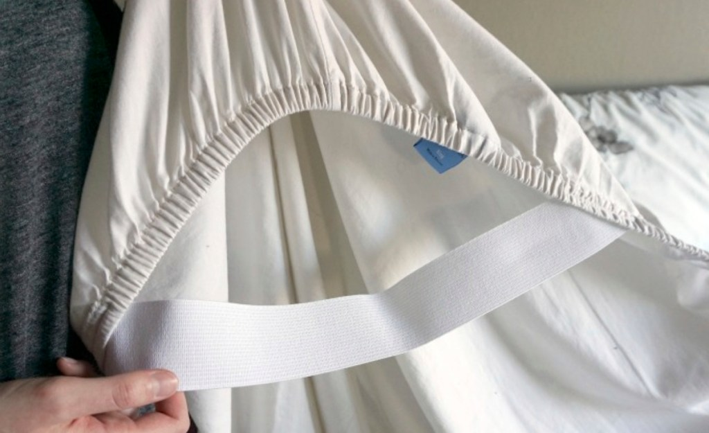 hand holding white fitted sheet with white elastic on corner