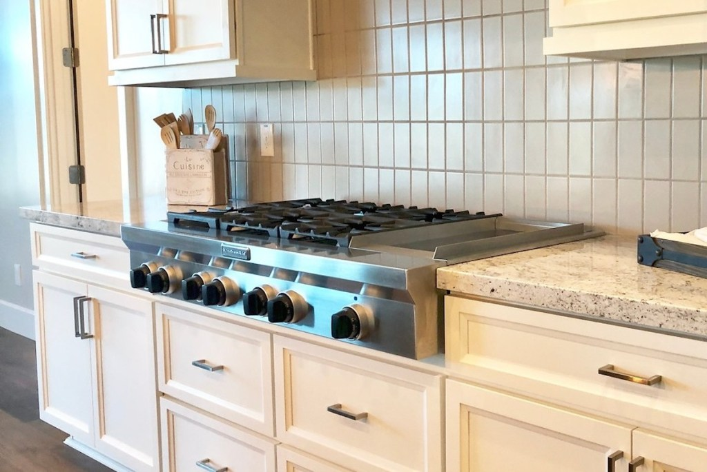 stainless steel kitchaid gas cooktop with black knobs on granite counter with cream shaker cabinets