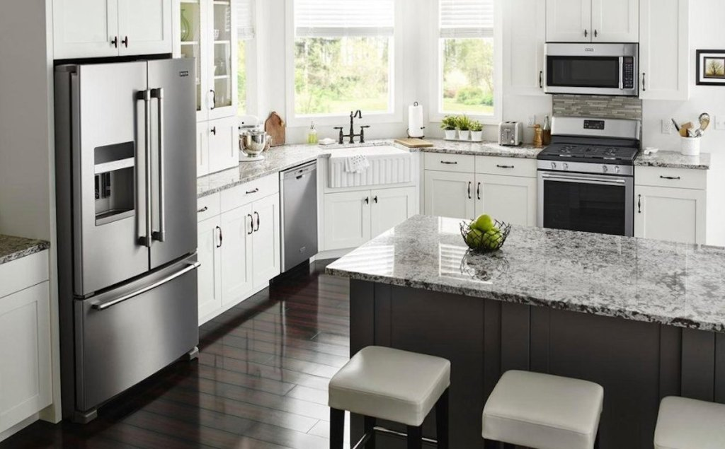 kitchen with white cabinets stone countertops cream stools and stainless steel appliances