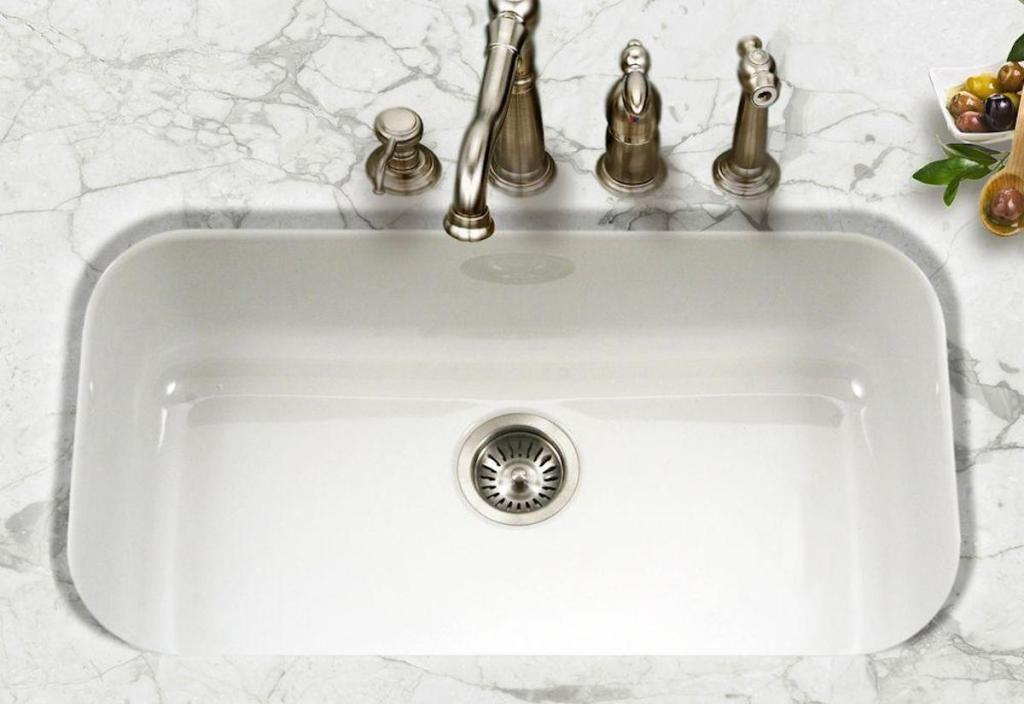 white glossy sink with stainless steel faucet and marble countertops