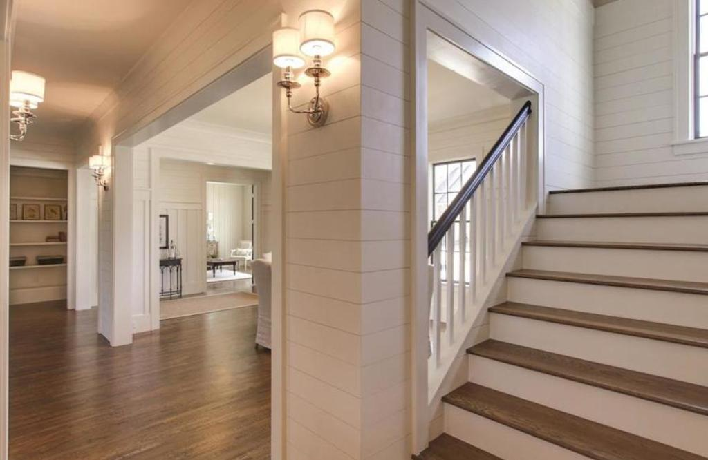 foyer in house with white shiplap walls and open floor plans with white walls and large wood staircase