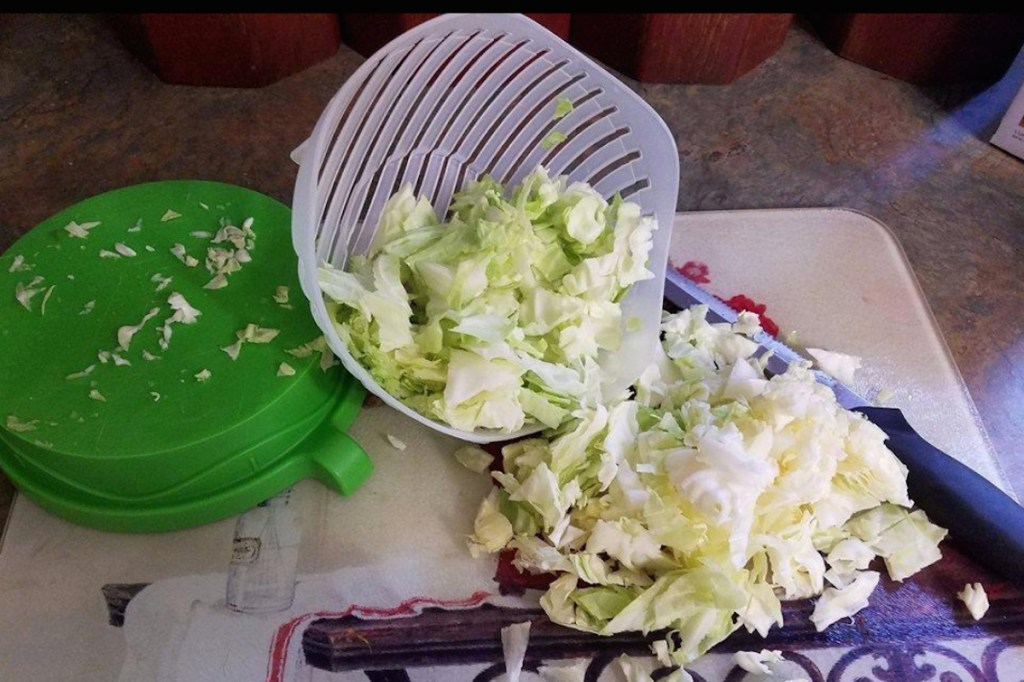 sliced salad in bowl with green lid spilling on counter