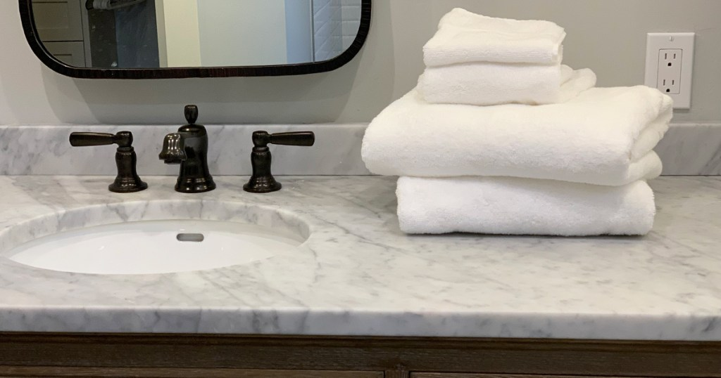 a stack of luxury towels on a marble counter