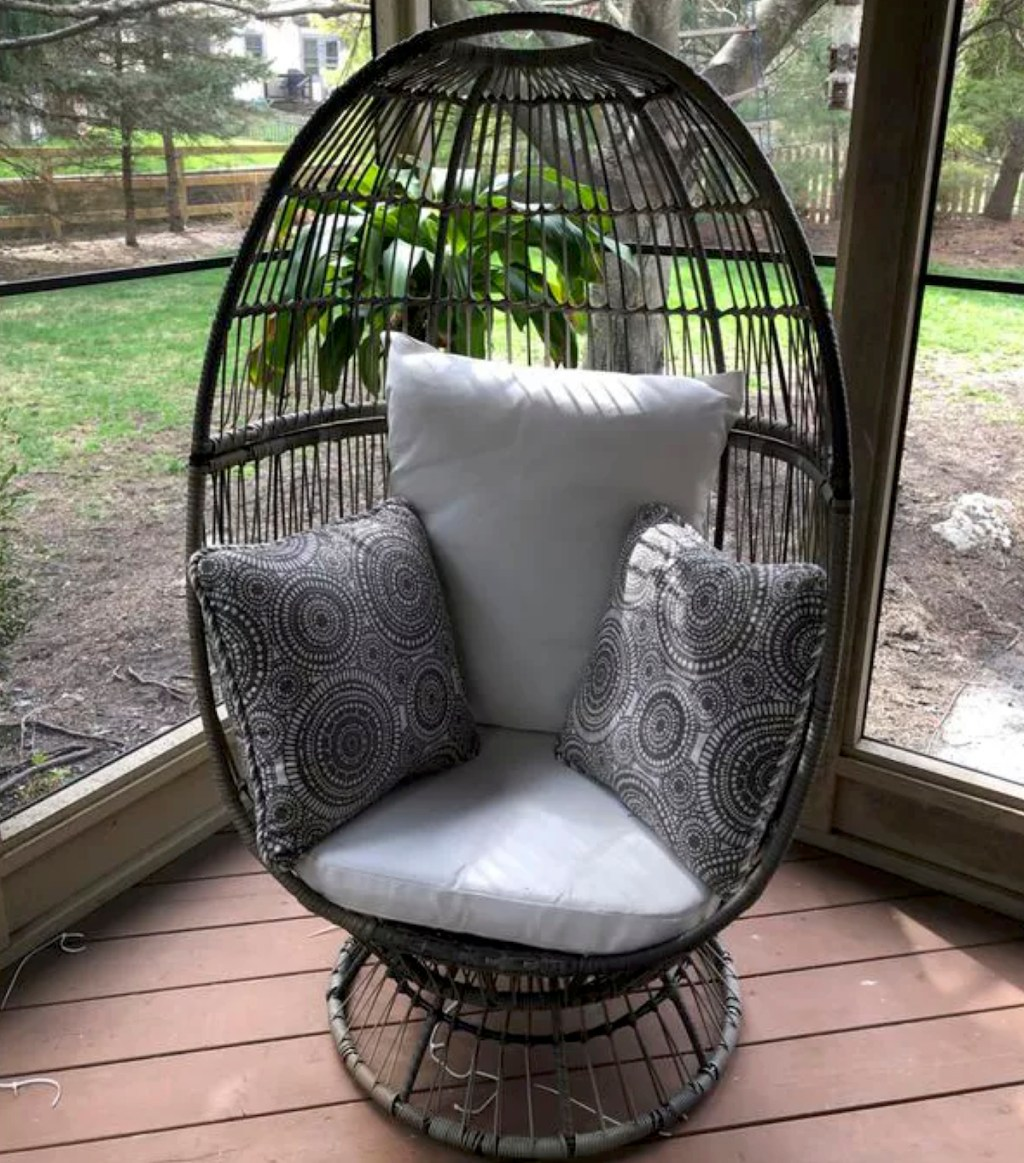 tall black egg chair with stand and white cushions decorative pillows