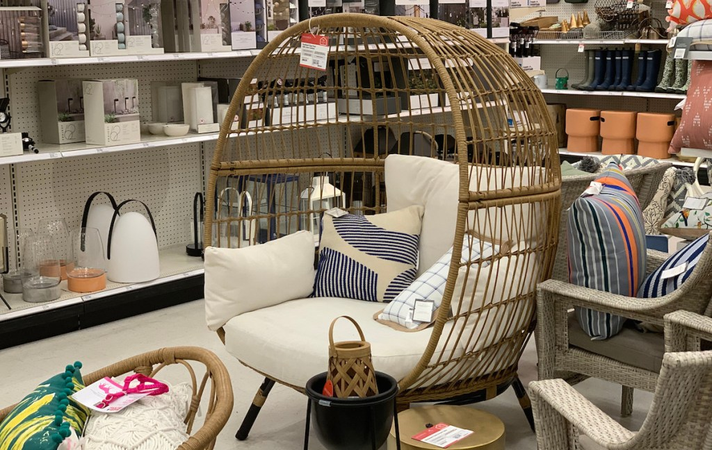 egg chair with white cushions and pillows sitting in store