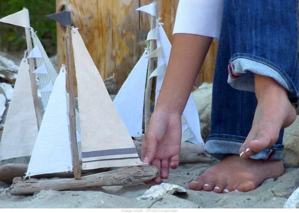 person holding driftwood sailboats on sandy beach