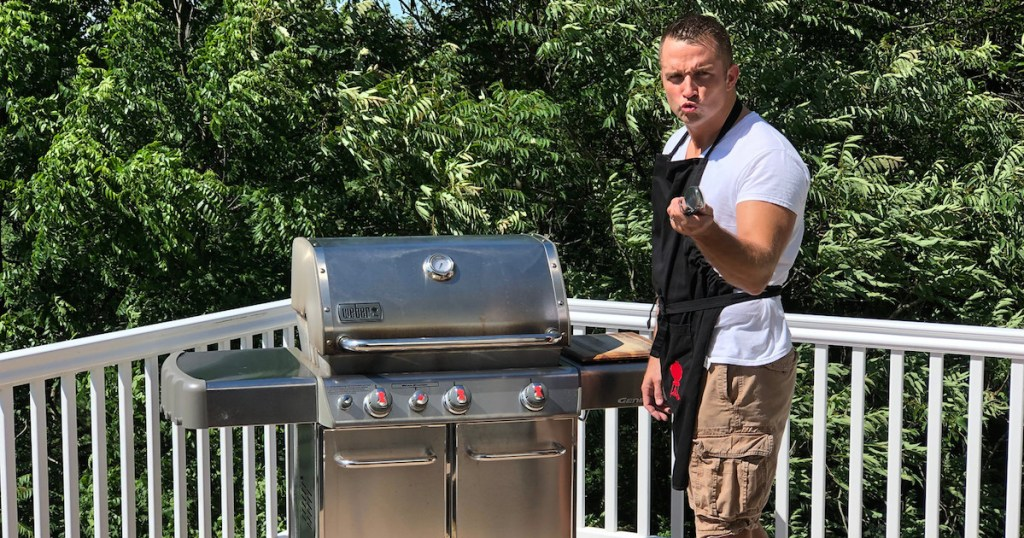 man standing next to stainless steel weber grill outside