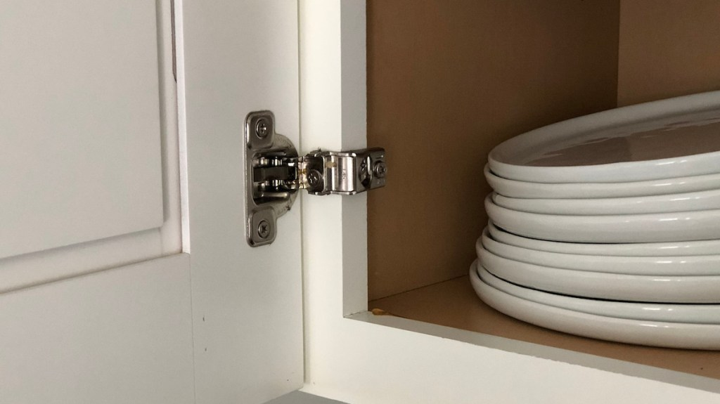 white cabinet with plates and silver hinges on door