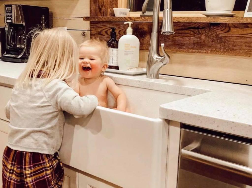 girl giving baby a bath in white farmhouse sink